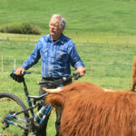 Rancher with a mountain bike, and his Scottish Highlander cattle